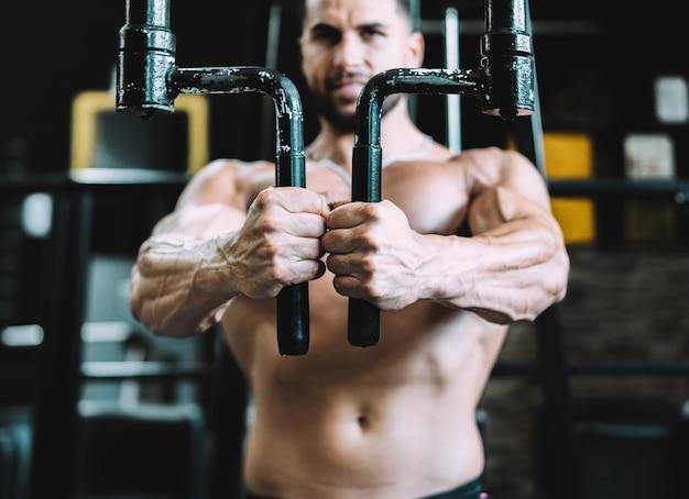 Selectieve focus op de handen van een man die traint op een machine in een sportschool