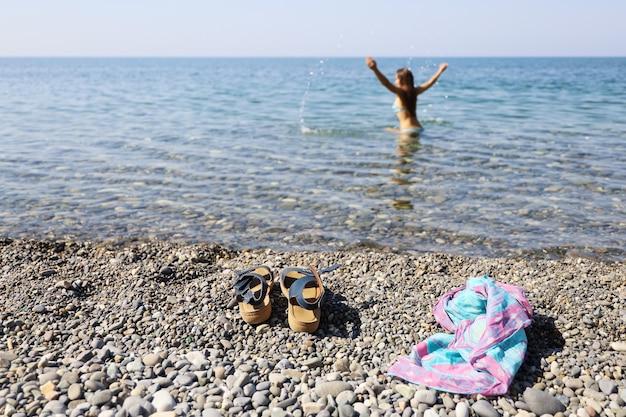 Selectieve focus op de voorgrond van de dingen van een vrouw die alleen in de zee spettert