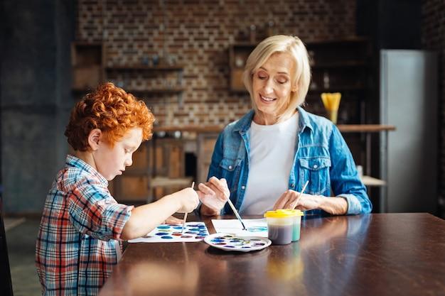 Selectieve focus op een geconcentreerde jongen met krullend haar die naast zijn positief ingestelde oma zit en een abstract beeld schildert terwijl hij allebei vrije tijd thuis doorbrengt.