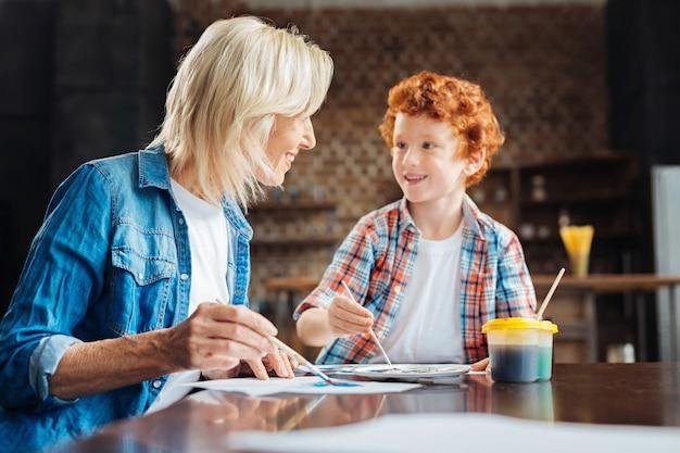 Selectieve focus op een positief ingestelde oudere dame die lacht terwijl ze naar haar schattige roodharige zoon kijkt die haar iets vertelt terwijl ze allebei thuis aan hun meesterwerken werken.
