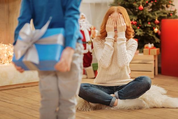 Selectieve focus op een verbaasde rijpe dame die haar ogen sluit van opwinding terwijl ze wacht op een kerstcadeau van haar opmerkzame zoontje.