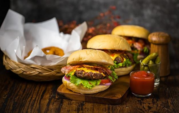 Selectieve focus op hamburgers met runderburgers, gebakken uien, spinazie, ketchup, peper en kaas geserveerd bijgerechten op een houten bord met frisdrank.