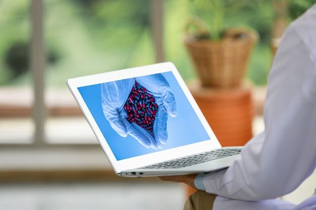 Selectieve focus op hand met medicijncapsule op laptopscherm terwijl de laptop in de hand is van doctor Premium Foto
