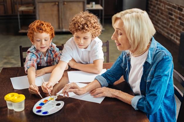 Selectieve focus op slimme kinderen die naast hun grootmoeder zitten en aquareltinten kiezen terwijl ze verfborstels vasthouden en nieuwe foto's maken.