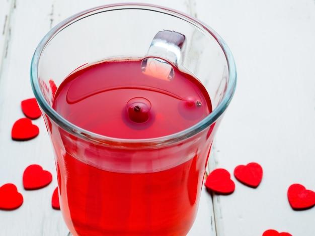 Selectieve focus op veenbessen in een fris drankje in een glazen beker op een witte houten achtergrond. veel kleine rode harten als symbool van valentijnsdag. detailopname. ruimte kopiëren.