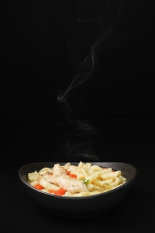 Selectieve focus op zelfgemaakte pittige kip noodlesoep met groenten en kruiden in een kom, close-up, donkere achtergrond.