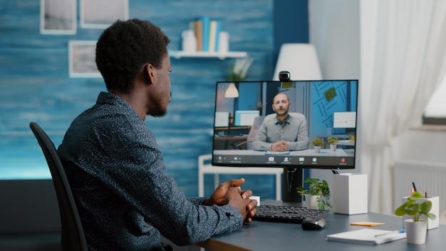 Selectieve focus op zwarte man met behulp van online videoconferentiegesprek in gesprek met zijn collega