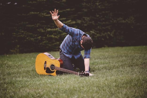 Selectieve focus shot van een emotionele man buiten met zijn gitaar