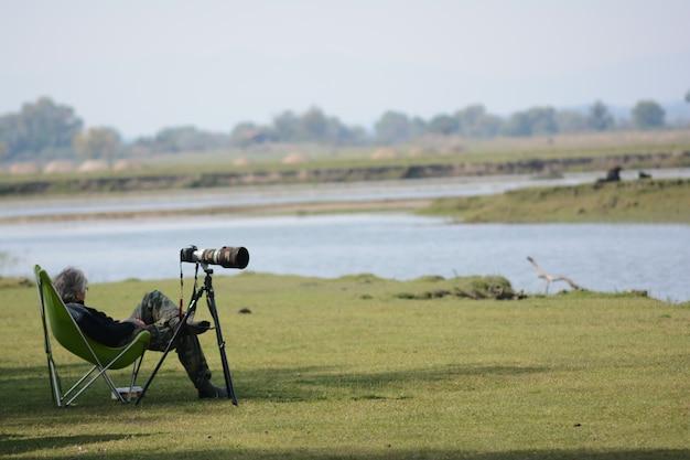 Selectieve focus shot van een oude man rustend op een klapstoel met zijn dslr-camera aan de zijkant
