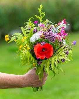Selectieve focus shot van iemand met een boeket verschillende bloemen buiten bij daglicht