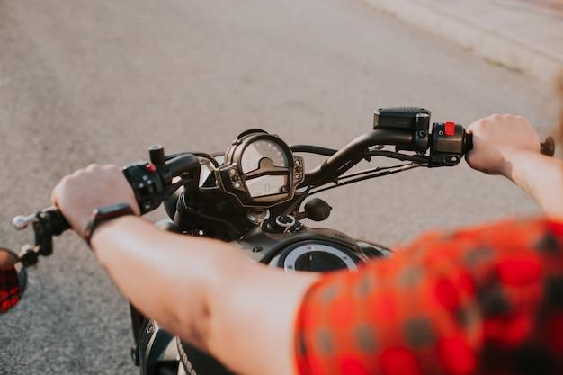 Selectieve focus shot van man handen rijden een zwarte motorfiets op een weg