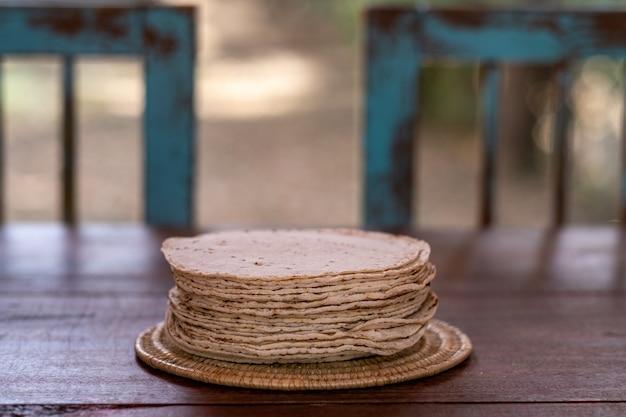 Selectieve focus van een geweven bord gevuld met vers zelfgebakken brood op een houten tafel