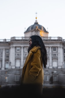 Selectieve focus van een jonge vrouw met bruine jas voor een stadsoriëntatiepunt