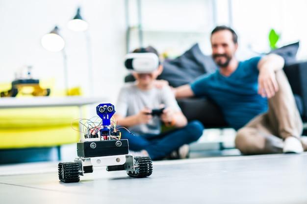 Selectieve focus van een kleine robot op de vloer met vader en zoon op de achtergrond
