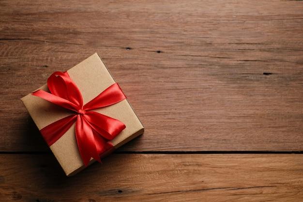 Selectieve focus van geschenkdoos met rood lint en liefdesvormig papier over rustieke houten tafel, bovenaanzicht plat gelegd.