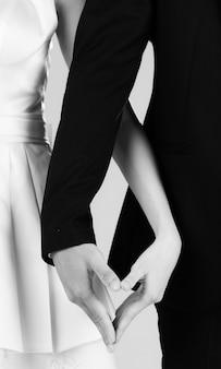 Selectieve focus van handen van bruid en bruidegom die samen een hartteken maken concept voor pre-huwelijksfotografie.