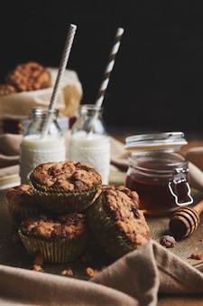 Selectieve focus van heerlijke kerstkoekjesmuffins op een bord met honing en melk