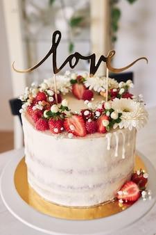 Selectieve focus van heerlijke witte bruidstaart met rode bessen, bloemen en taarttopper