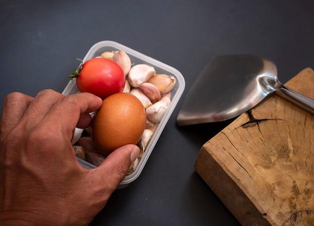 Selectieve focus van in de hand gehouden eieren met tomaten en knoflook in een