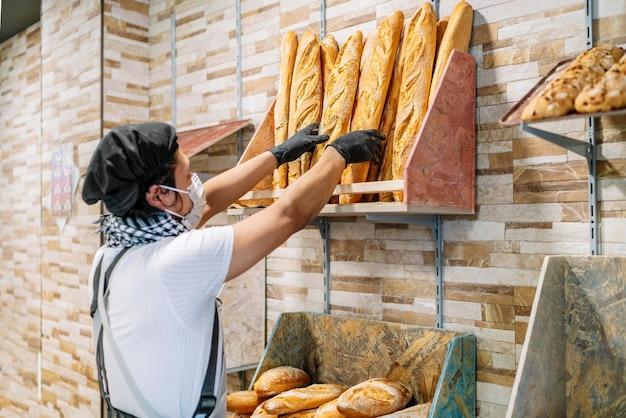 Selectieve focus van latino bakker rekken vers gebakken brood met een beschermend gezichtsmasker
