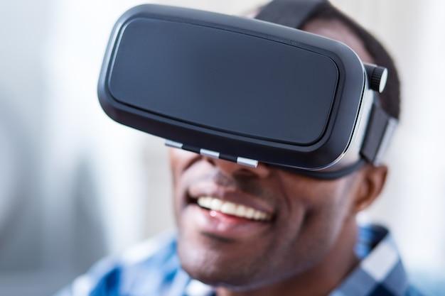 Selectieve focus van moderne 3d-bril die wordt gedragen door een vrolijke, mooie knappe man terwijl hij in virtual reality is