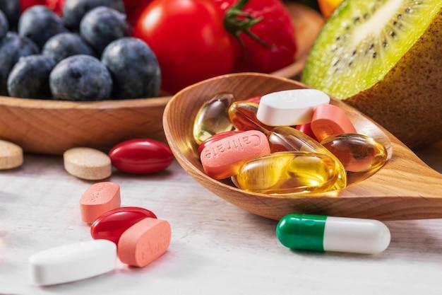 Selectieve focus van vers fruit en groenten met verschillende medicijnen op een houten lepel Premium Foto
