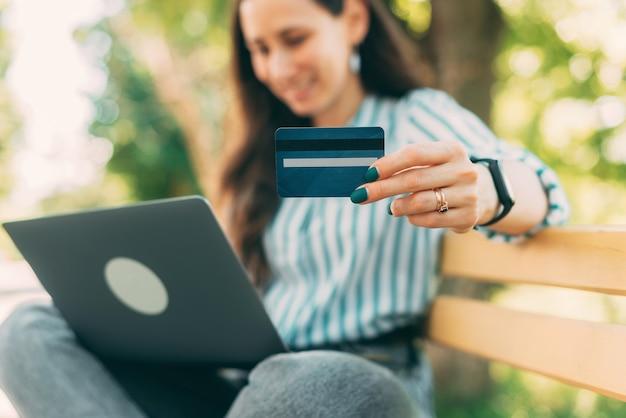 Selectieve focus van vrouw met blauwe creditcard buitenshuis