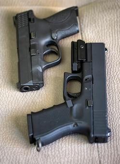 Selectieve focus van zwarte geweren pistolen met munitie. misdaad, maffia, terrorisme. semi-automatisch pistoolvuurwapen ligt tegen elkaar op de achtergrond van de bank. camera is gericht op de loop van het pistool