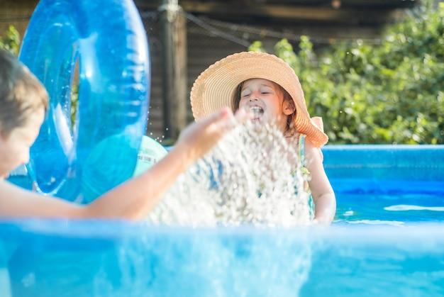 Selectieve focus, vervagen devoku. kinderen spelen in de hete zomer met een bal in het zwembad. meisje en jongen buitenshuis