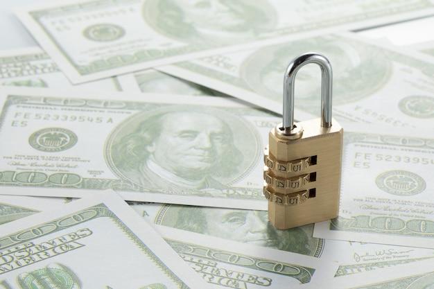 Selectieve focusopname van bankbiljetten van honderd dollar en een hangslot
