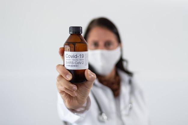 Selectieve focusopname van een vrouwelijke arts die een fles vaccin tegen het coronavirus vasthoudt