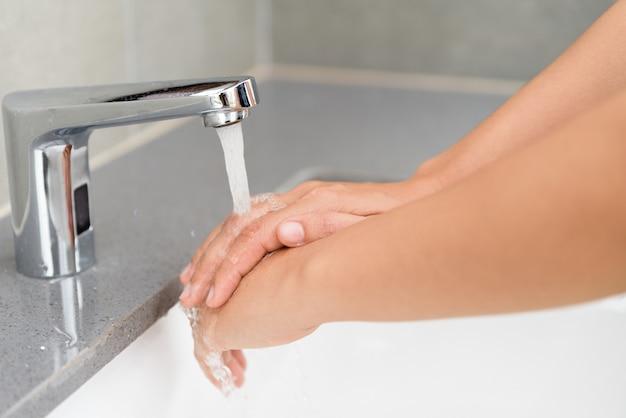 Selectieve nadruk van de handen van de vrouwenwas met zeep onder de tapkraan met water in bathr