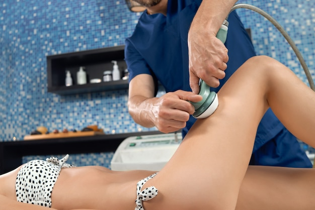 Selectieve nadruk van masseurhanden die massage van benen doen