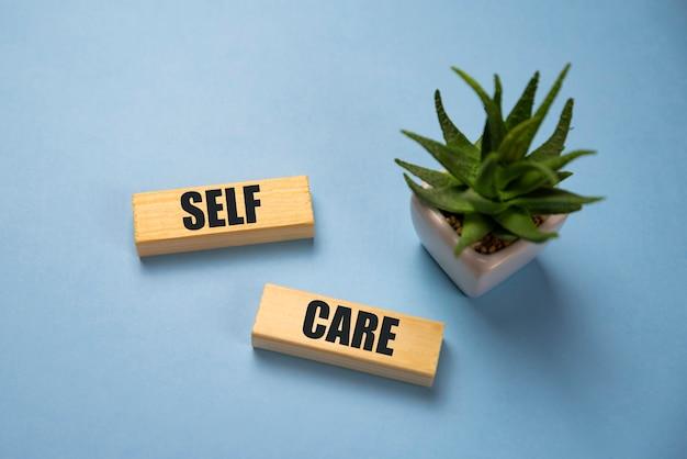 Selfcare woord op lightbox op blauwe achtergrond plat lag. zorg voor jezelf.