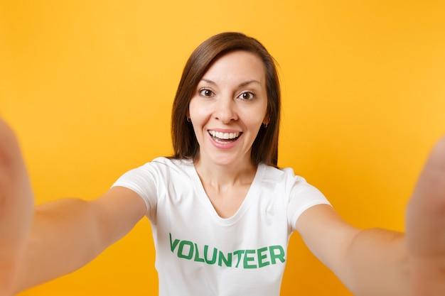 Selfie afbeelding van gelukkig lachende tevreden vrouw in wit t-shirt met schriftelijke inscriptie groene titel vrijwilliger geïsoleerd op gele achtergrond. vrijwillige gratis hulp, liefdadigheidswerkconcept.