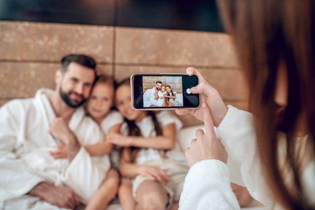 Selfie. familie in witte gewaden in bed liggen en selfie maken