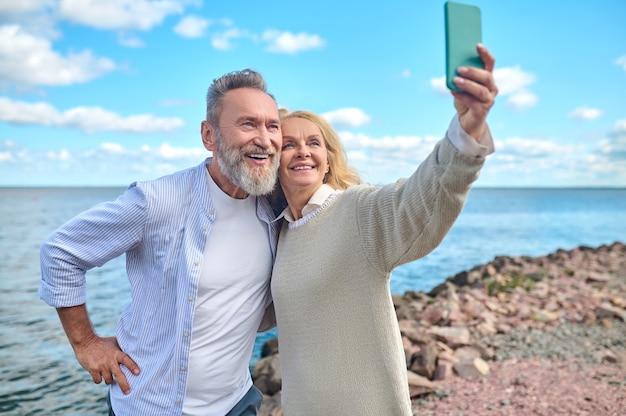 Selfie in de natuur. blonde vrouw met smartphone in haar uitgestrekte hand die overdag selfie maakt met lachende bebaarde man buiten