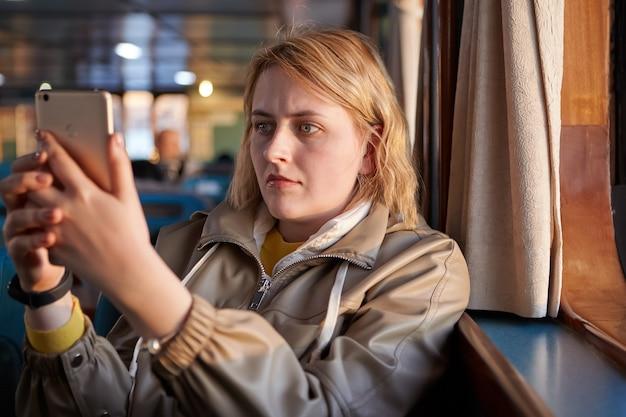Selfie in passagierscabine van veerboot jonge blanke vrouw met serieus gezicht maakt foto's van zichzelf