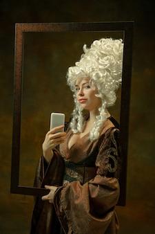 Selfie in spiegel. portret van middeleeuwse vrouw in vintage kleding met houten frame op donkere achtergrond. vrouwelijk model als hertogin, koninklijk persoon. concept vergelijking van tijdperken, modern, mode, schoonheid.