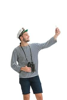 Selfie maken. kaukasische mannelijke matroos in uniform op witte studiomuur.