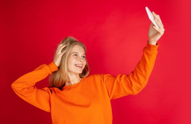 Selfie maken. portret van jonge blanke vrouw geïsoleerd op rode studio achtergrond met copyspace. mooi vrouwelijk model. concept van menselijke emoties, gezichtsuitdrukking, verkoop, advertentie, jeugd. folder
