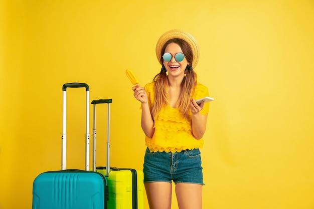 Selfie maken voordat je op reis gaat. het portret van de kaukasische vrouw op gele studioachtergrond. prachtig model in dop. concept van menselijke emoties, gezichtsuitdrukking, verkoop, advertentie. zomer, reizen, toevlucht.