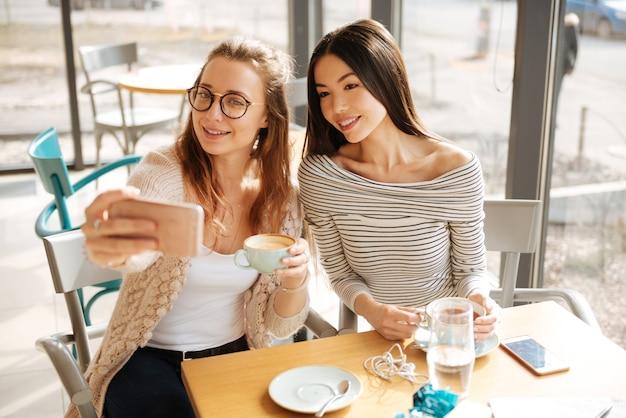 Selfie met bestie.twee mooie jonge vriendinnen nemen selfie tijdens hun ontmoeting in de cafetaria.