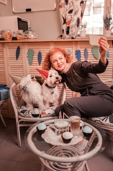 Selfie met honden. stralende roodharige vrouw die van honden houdt en enorm selfie maakt met haar schatjes