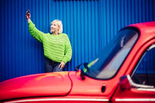 Selfie mobiele telefoon gelukkige mensen technologie concept met mooie blonde met groene kleding en rode vintage auto en blauwe muur. moderne millennial persoon trendy levensstijl en onafhankelijkheid