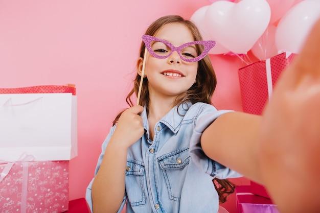 Selfie portret geweldig meisje met paars masker op gezicht lachend naar camera op roze achtergrond. gelukkige verjaardag vieren, kleurrijke ballonnen met grote geschenkdozen, positiviteit uitdrukken