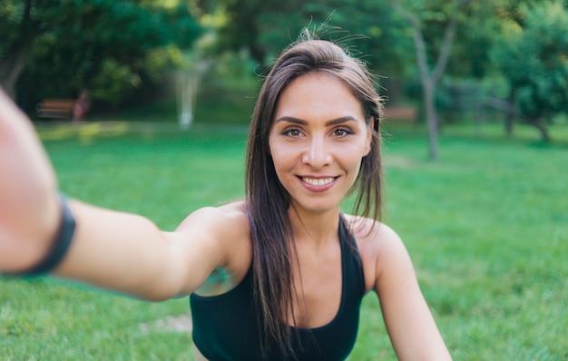Selfie portret jonge vrolijke fit vrouw in sport top glimlachend buiten in park