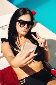 Selfie-portret van brunette vrouw met lang haar bij zwembad. genieten van een luxe vakantie in een resorthotel.