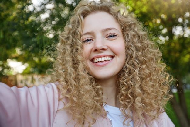 Selfie-portret van charmante jonge mooie blonde vrouw met krullend haar, in een goed humeur