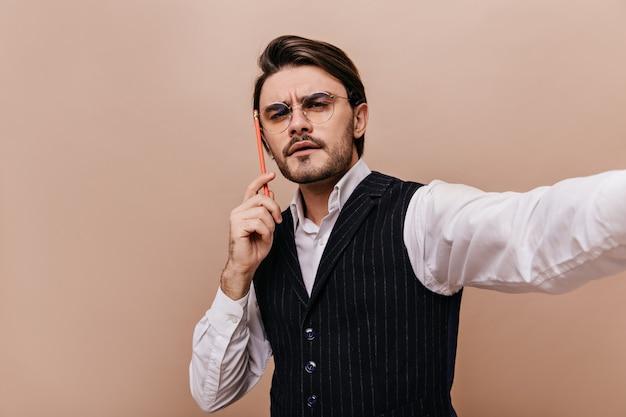 Selfie-portret van denkende man met donkerbruin haar en borstelharen, bril, wit overhemd en klassiek vest, potlood in de buurt van hoofd houden en selfie maken tegen effen beige muur